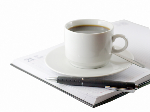 Cup of Coffee with pen and note book next to it